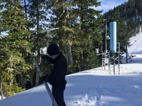 Trevor Dickinson holding a snow tube, used for taking a core snow sample to measure density by weighing the tube